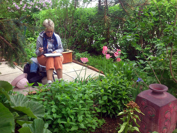Claudette is in the zone, sketching a large vase and surrounding plants.